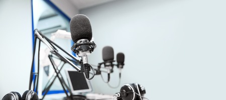 technology and audio equipment concept - microphones at recording studio or radio station