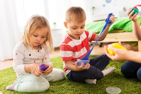 Kinder mit Modelliermasse oder Schleimen zu Hause