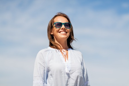 happy smiling woman in sunglasses over sky