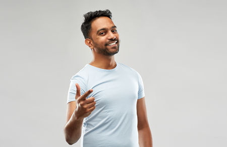 smiling indian man pointing finger at you