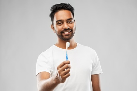 indian man with toothbrush over gray background Stock Photo - 112716207
