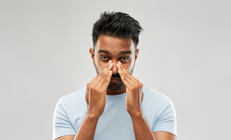 indian man rubbing nose