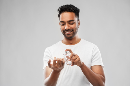 happy indian man with perfume over gray background