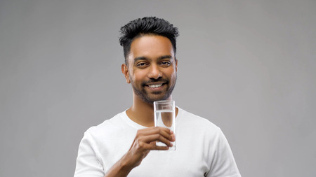 happy young indian man drinking water from glass Standard-Bild