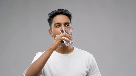 happy young indian man drinking water from glass 版權商用圖片