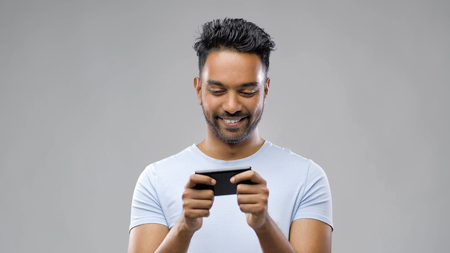 happy indian man playing game on smartphone Stock Photo
