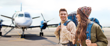 couple of tourists with backpacks over plane