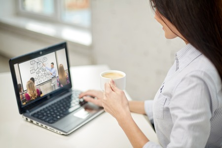 Mujer con café viendo webinar en portátil