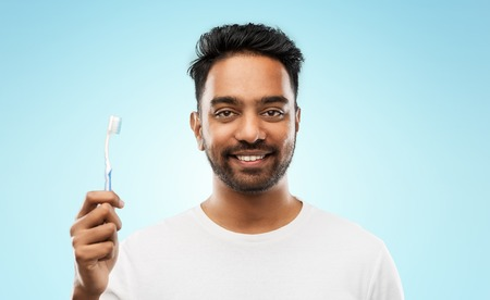 indian man with toothbrush over blue background