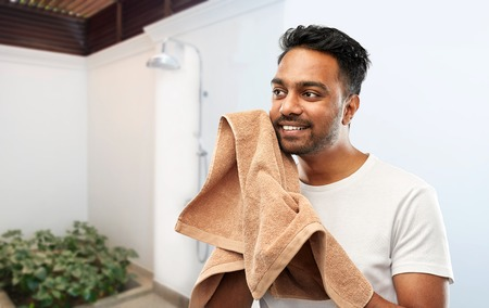 smiling indian man with bath towel over shower Stock Photo