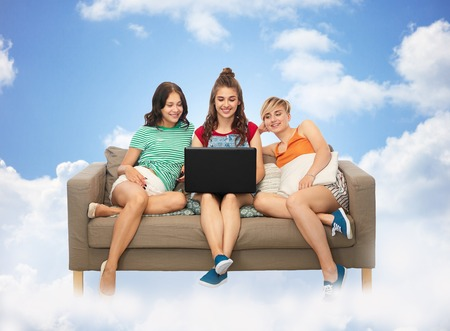 female friends with laptop computer over clouds Stock fotó