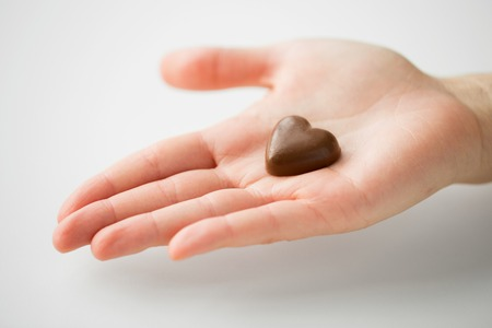 close up of hand with heart shaped chocolate candy Stock Photo