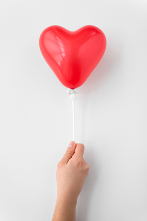 close up of hand holding red heart shaped balloon