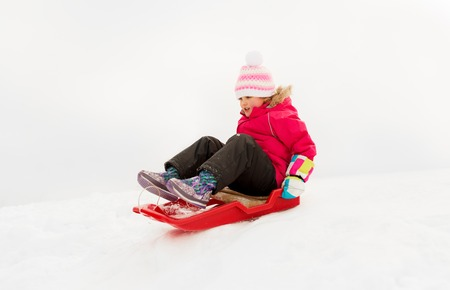 happy little girl sliding down on sled in winter Banco de Imagens