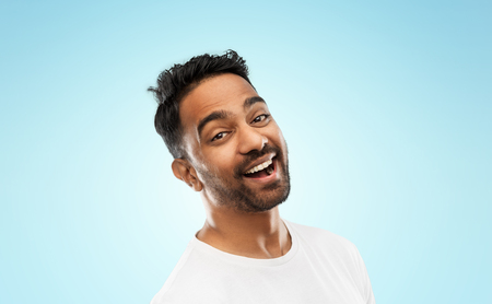 young laughing indian man over blue background
