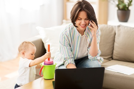 working mother with baby calling on smartphone Stockfoto
