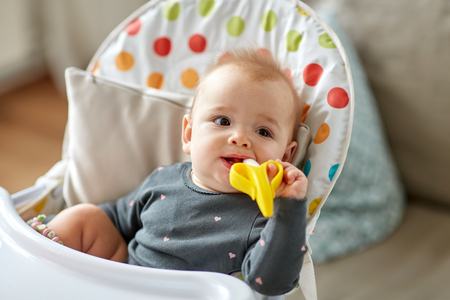 baby girl with teether toy in highchair at home