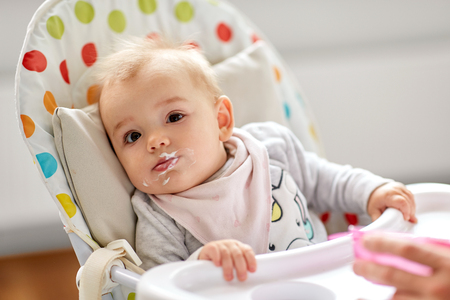 little baby girl eating in highchair at home Stock Photo