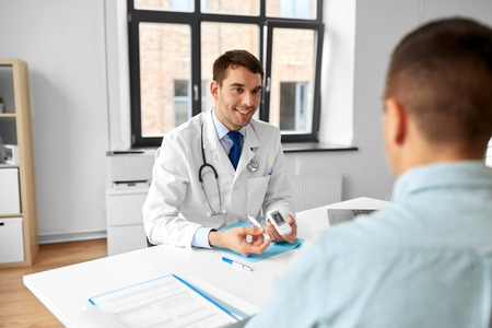 doctor with glucometer and patient at hospital