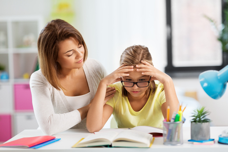 mother helping daughter with difficult homework Stok Fotoğraf
