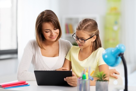 mother and daughter with tablet pc doing homework 스톡 콘텐츠 - 112982320