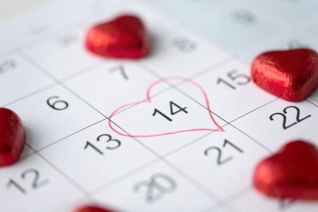 valentines day and holidays concept - close up of calendar sheet with marked 14th february date and red heart shaped chocolate candies Stock fotó