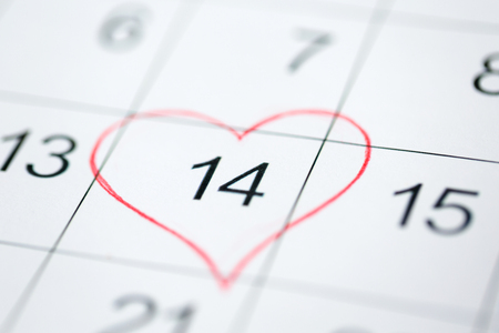 valentines day and holidays concept - close up of calendar sheet with 14th february date marked by red heart shape Фото со стока