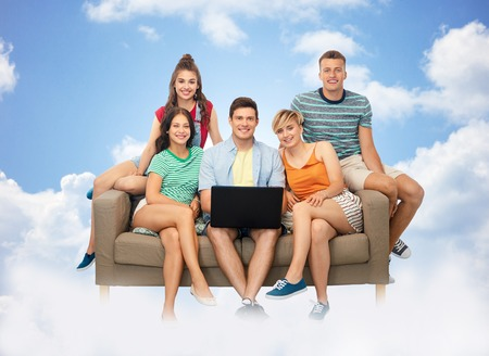 friends with laptop computer on sofa over clouds Stock fotó