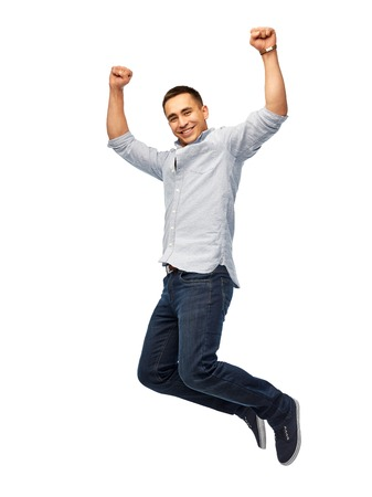 happy young man jumping over white background 版權商用圖片