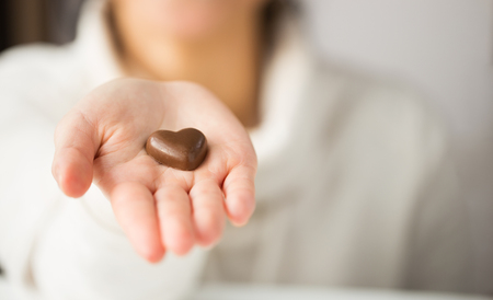 close up of hand with heart shaped chocolate candy Stockfoto