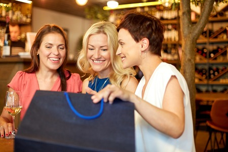 women with shopping bags at wine bar or restaurant