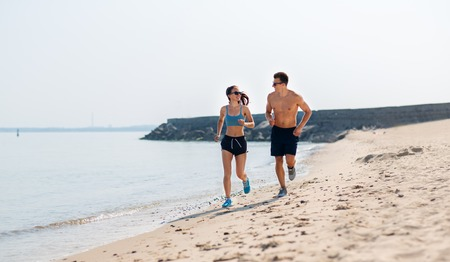 couple in sports clothes running along on beach 写真素材