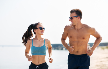 couple in sports clothes running along on beach 免版税图像