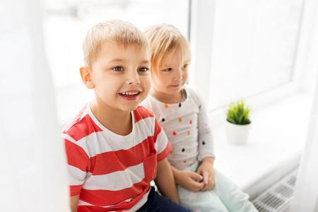 happy little kids sitting on window sill