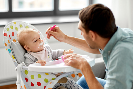 father feeding baby in highchair at home