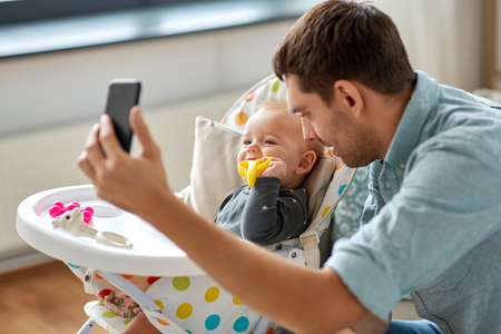 father with baby daughter taking selfie at home