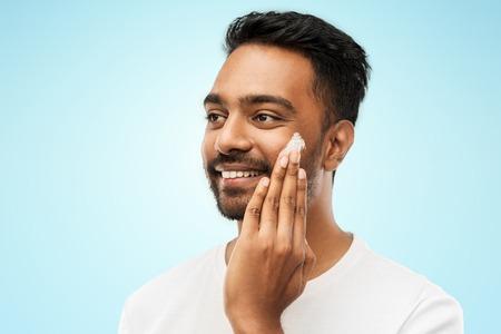 얼굴에 크림을 바르는 행복한 인도 남자