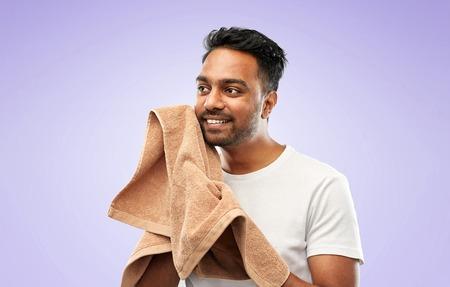 indian man using bath towel over violet background Banque d'images