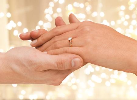 primo piano delle mani di coppia con anello di fidanzamento