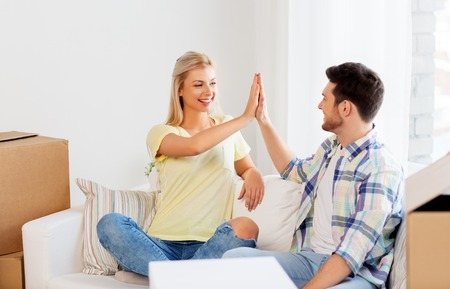 happy couple with boxes moving to new home Stock Photo