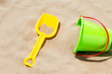 close up of toy bucket and shovel on beach sand