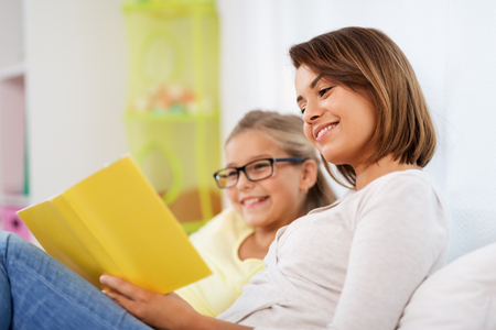 happy girl with mother reading book at home Stock Photo