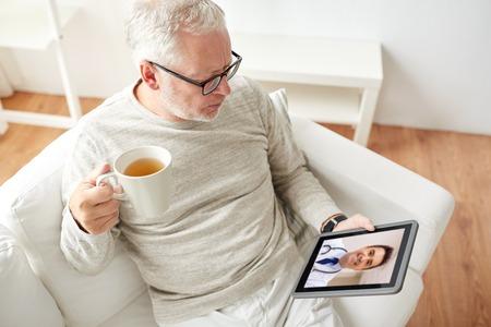 senior man met videogesprek met arts op tablet