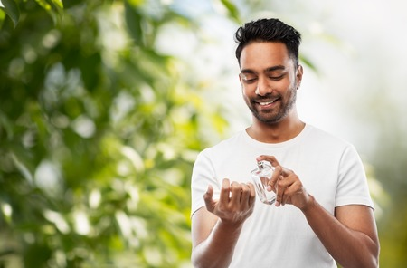 indian man with perfume over natural background