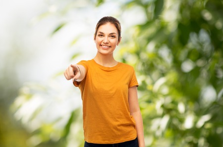 teenage girl pointing at you over natural backdrop
