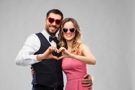 couple in sunglasses making hand heart gesture
