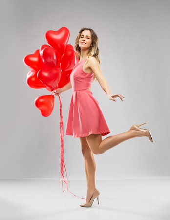 happy young woman with red heart shaped balloons