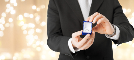 valentines day, proposal and engagement concept - close up of man with diamond ring in little red gift box over festive lights background