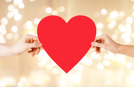 health, love and relationships concept - closeup of couple hands with big red heart over festive lights background Stock Photo