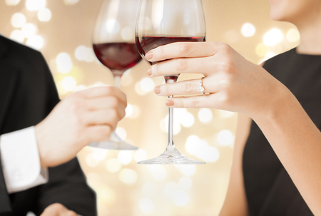 valentines day, celebration and engagement concept - close up of couple hands clinking champagne glasses 스톡 콘텐츠